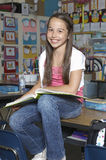 Girl Sitting On Desk With Book Royalty Free Stock Image