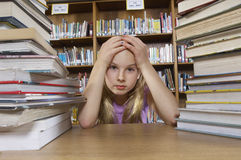 Girl Sitting At Desk With Books Stock Photo
