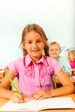 Girl sitting at desk in classroom and writing Stock Photography
