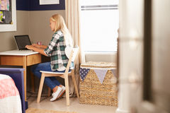 Girl sitting at a desk in her bedroom using laptop Royalty Free Stock Image