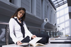 Girl sitting on desk in library Stock Photography