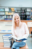 Girl sitting on the desk with pile of books Royalty Free Stock Photography