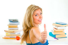 Girl sitting at desk and showing thumbs up Royalty Free Stock Photo