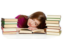 Girl sitting at the desk and sleeping on a book Stock Photos
