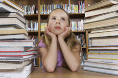 Girl Sitting At Desk With Stack Of Books Stock Photography