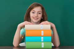 Girl Sitting At Desk With Stack Of Books Royalty Free Stock Image