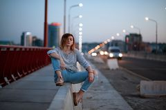 The girl is sitting on the divider near the cars on the bridge stock photography