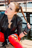 Girl sitting on the dock and holding a scythe Royalty Free Stock Photography