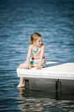 Girl sitting on a dock at lake Stock Photography