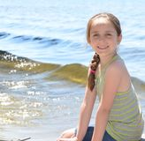 Girl sitting on a dock Stock Images