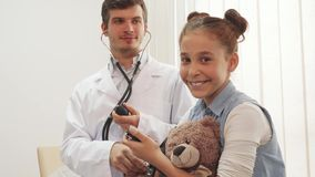 An experienced doctor measures her patient`s blood pressure. The girl is sitting at doctor`s appointment. In her hands she holds her soft bear and a stopwatch stock images