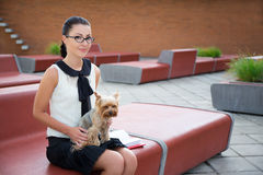 Girl sitting with dog yorkshire terrier in park Stock Image