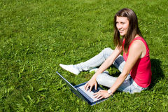 Girl sitting down on the grass  with her laptop Royalty Free Stock Image