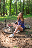 Girl sitting down with pain in knee joints after biking on bicycle in park stock photography