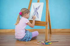 Girl sitting down painting a picture Stock Photography