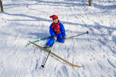 Girl sitting down on the snow learning skiing Stock Images