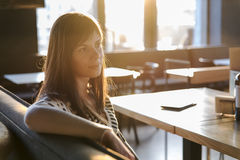 A girl sitting and dreaming in the cafe Stock Photography
