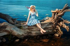 Girl sitting on a driftwood Stock Photography