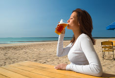 Girl sitting&drinking on a beach-1 Royalty Free Stock Image