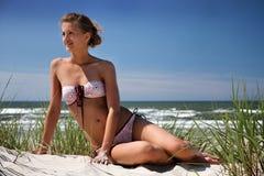 Girl sitting on a dune. Beautiful girl enjoy sun in Sventoji beach near Baltic sea, Lithuania Stock Photo