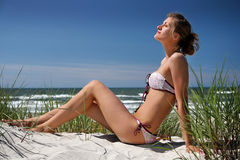 Girl sitting on a dune. Beautiful girl enjoy vacation in Sventoji beach near Baltic sea, Lithuania Stock Photography