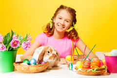 Girl sitting with Easter eggs and rabbit at table Stock Photo