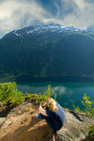 Girl sitting on the edge of the fjord. ocean and mountains. Stock Photography