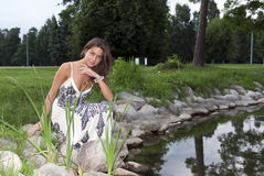Girl sitting on the edge of the pond Royalty Free Stock Photos