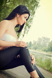 Girl sitting on edge of pond. Stock Images