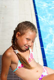 Girl sitting on the edge of the pool Stock Photo