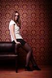 Girl sitting on edge of sofa Royalty Free Stock Photos