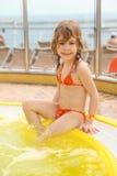 Girl sitting on edge of swimming pool stock image
