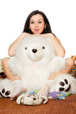 Girl sitting in an embrace with a large teddy bear Royalty Free Stock Image