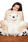Girl sitting in an embrace with a teddy bear Stock Photos