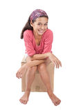 Girl sitting on empty cardboard box. Royalty Free Stock Photo