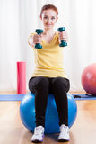 Girl sitting on exercise ball and lifting weights Stock Photo