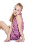 Girl sitting in a fancy purple dress Royalty Free Stock Image