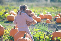 Girl sitting at the farm on a big pumpkin hugging teddy bear Royalty Free Stock Image
