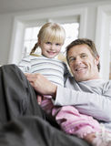 Girl Sitting On Father's Lap In House Royalty Free Stock Photo