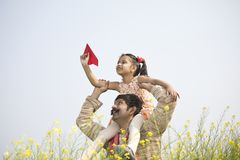 Girl sitting on father`s shoulder and throwing paper airplane. Rural Indian girl sitting on father`s shoulder and playing with toy paper airplane in field royalty free stock images