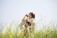 Girl sitting on father`s shoulder and throwing paper airplane royalty free stock photo