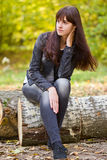 Girl sitting on a felled tree Stock Photo