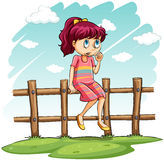 A girl sitting on the fence Royalty Free Stock Images