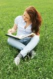 Girl sitting in the field Stock Image