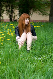 Girl sitting on a field Stock Images