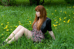 Girl sitting on a field Stock Image