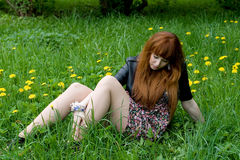 Girl sitting on a field Stock Photos