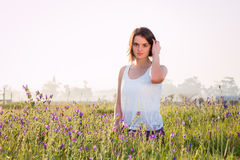 Girl sitting in field of flowers. Happy stock photo