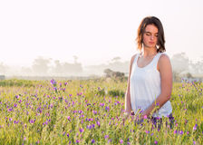 Girl sitting in field of flowers. Looking down royalty free stock image
