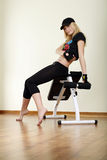 Girl sitting on fitness machine Stock Photos